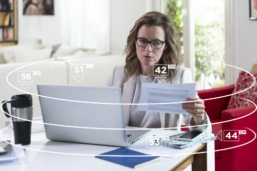 Une femme quadragénaire équipée de verre progressifs Varilux ® X Series ™assise à son bureau devant son écran d'ordinateur portable, tenant un document papier dans sa main gauche. Trois cercles autour d'elle avec les distances pour illustrer les adaptation de la vue de près.
